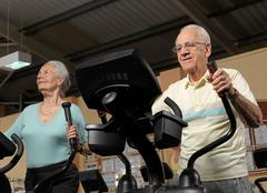 Senior couple training at gym Stock Photos
