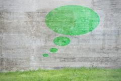 Green thought bubble on concrete wall - stock photo