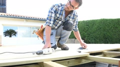 Carpenter building wooden deck using drill Stock Footage