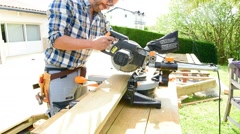Carpenter sawing planks for wooden deck Stock Footage