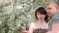 Young couple in love makes selfie in a public park: smart phone.  A flowering - stock footage