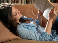 Girl, 14 reading - stock photo