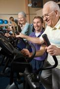 Seniors training at gym with instructor Stock Photos