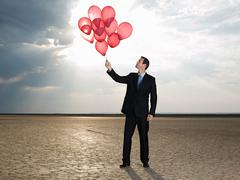 Businessman holding a bunch of red balloons - stock photo