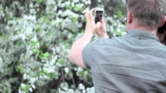Young couple in love makes selfie in a public park: smart phone.  A flowering Stock Footage