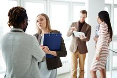 Office workers discussing plans in working environment - stock photo