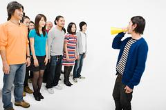 Crowd and man with loudspeaker - stock photo