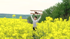 Happy boy goes with toy airplane cross the rape. Slow motion Stock Footage
