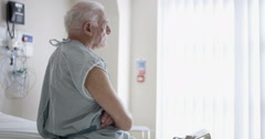 4K Friendly hospital doctor examining elderly patient in a private room - stock footage