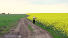 Boy running with toy airplane near the rape fields. Slow motion - stock footage