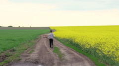 Cheerful child running with toy helicopter near the rape field. Slow motion - stock footage