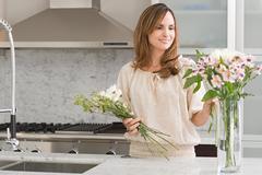 Hispanic woman flower arranging - stock photo