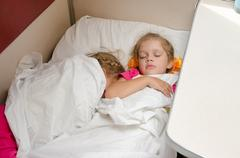 Two children sleep on the train on the same ground location in the second-cla - stock photo