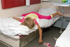 Little girl on the train lies flat on the lower second-class place car dangli - stock photo