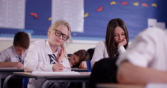 4k, Candid shot of two girls in a class studying alongside their classmates. - stock footage