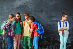 Offended schoolgirl standing at distance of her classmates gossiping against bla - stock photo