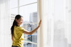 Japanese woman looking through a window - stock photo