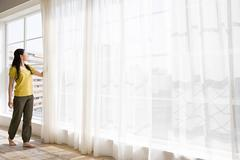 Japanese woman opening net curtains Stock Photos