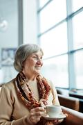 Smiling senior female with cup of tea sitting in arm-chair Stock Photos