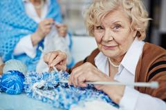 Elderly woman knitting and looking at camera Stock Photos