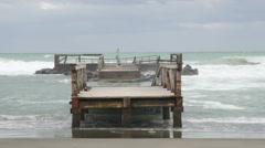 Italy, Rome, Tyrrhenian Sea - storm wind and waves splashing over broken pier - stock footage