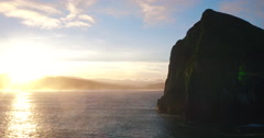 Aerial View Over Rocky Sea Cliffs Coastline with Amazing Sunrise Light Stock Footage