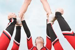 Cheerleaders performing routine Stock Photos