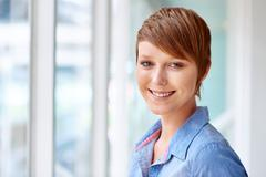 Smiling young modern woman in bright natural lighting Stock Photos