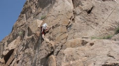 Young girl climbs on a rock in gear Stock Footage