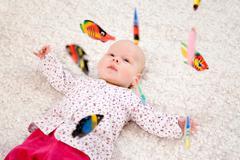 baby lying beneath mobile toy - stock photo