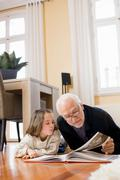 Old man reading book to young girl Stock Photos