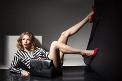 Attractive model lying with bare legs in red heels and black fashion bag - stock photo