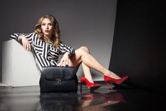 Elegant blonde woman in red heels with fashion bag Stock Photos