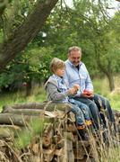 Man and boy with apples, sitting on logs - stock photo