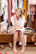 Woman sitting in her closet - stock photo