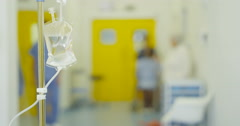 4K Blurred view of hospital staff & patients focus on saline drip in foreground Stock Footage