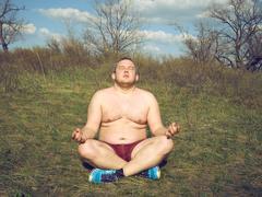 Fat man doing yoga Stock Photos