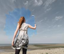 Young woman painting grey sky blue - stock photo