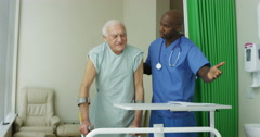4K Caring medical workers in hospital assisting elderly man in a private room - stock footage