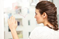 Woman looking sadly at a painted heart. - stock photo
