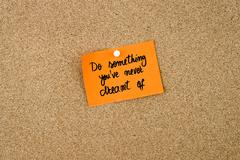 Do Something You've Never Dreamt Of written on orange paper note - stock photo