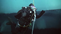 Divers emerge from the depths of the Arctic Ocean at the North Pole. - stock footage