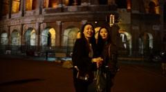 Coliseum at Night. Girls Korean, Japanese, Chinese have fun making photo selfie Stock Footage