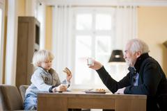 Grandson and grandfather eating Stock Photos