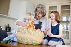 grandmother and grandchildren packing - stock photo