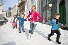 Scandinavian children running in snow - stock photo