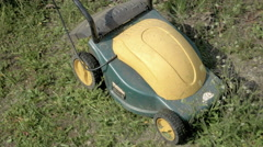 Mowing grass in the garden with electrical machine Stock Footage