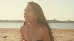 Happy woman sitting on a sand beach  in summer backlit in golden sunshine glow Stock Footage