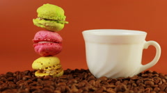 Macrons with cup of coffee on a brown background Stock Footage
