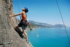 Woman rock climbing, bay in background Stock Photos